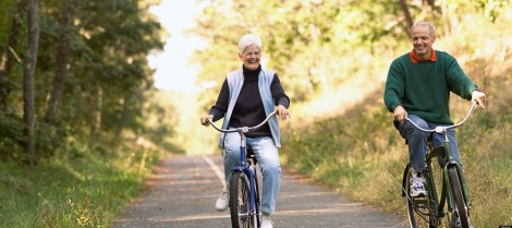 Senior couple cycling along bike path in woods