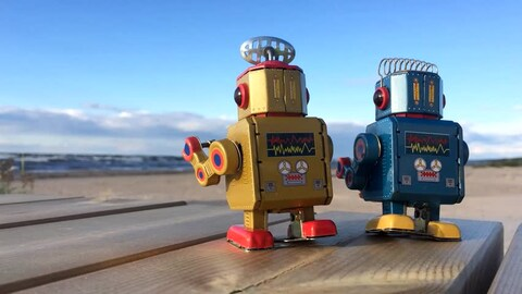two old school box style robots on a table near the beach looking at the water in the distance