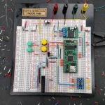 prototyping a microcontroller on a breadboard. Random bits of wires can be seen around the black table.