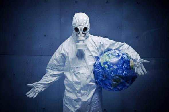 Person in gas mask and full PPE holding a globe