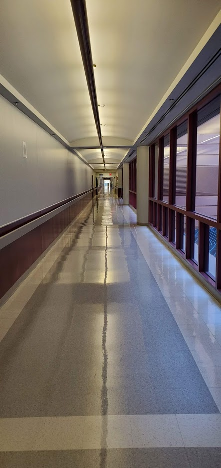 A seemingly endless hallway in a hospital. The floors have a shine to them and the yellow tint to the lighting makes it feel older than it probably is.