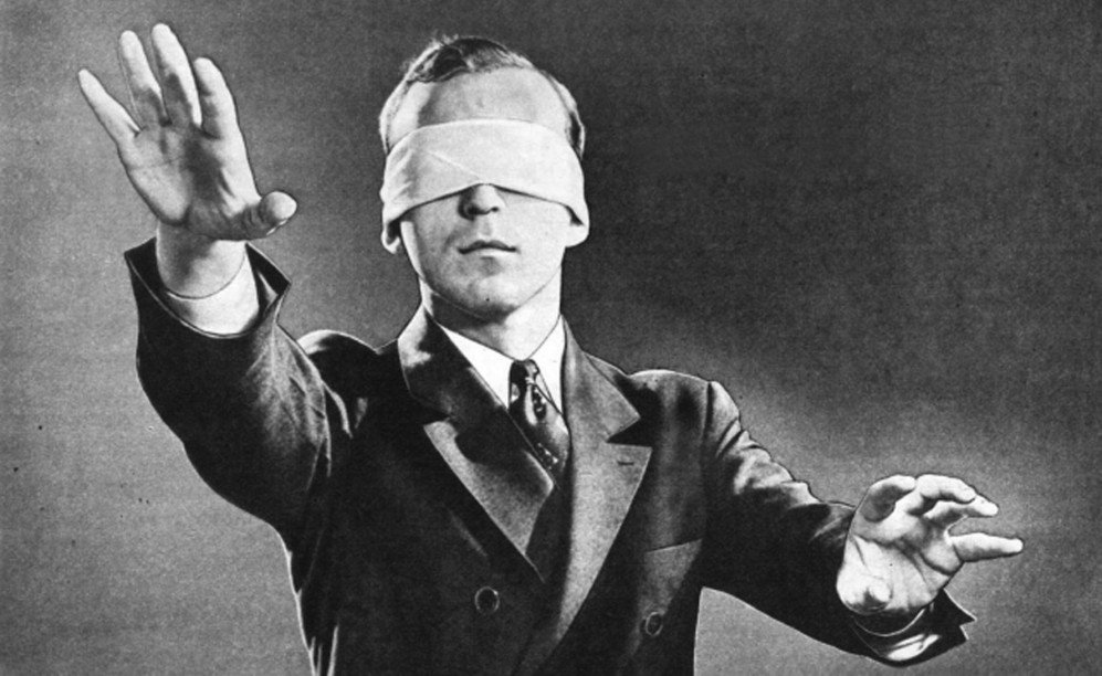 Old black and white photo of blindfolded man in a suit reaching out in front of him.